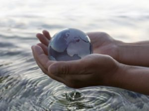 hands holding globe over water